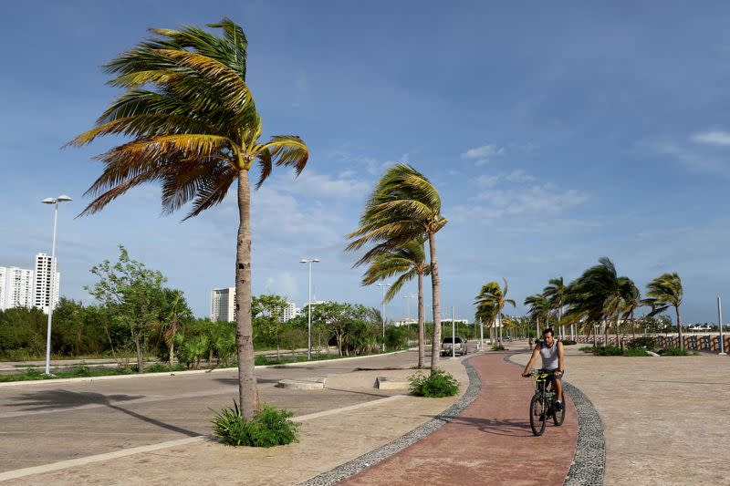 FILE PHOTO: A man rides his bicycle while palm trees sway in the wind as Hurricane Zeta approaches Cancun