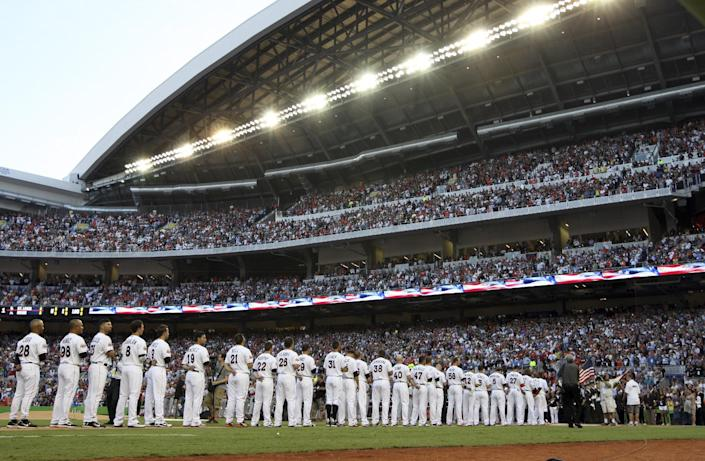 The Miami Marlins stand for the national anthem at the new Marlins Park before the Opening Day baseball game against the St. Louis Cardinals, Wednesday, April 4, 2012, in Miami. (AP Photo/Lynne Sladky)