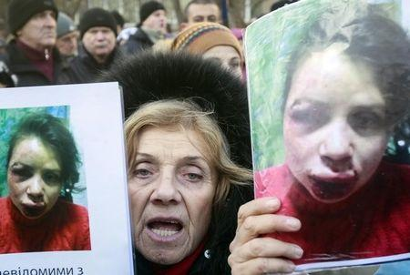 A protester holds pictures of journalist Tetyana Chornovil, who was beaten and left in a ditch just hours after publishing an article on the assets of top government officials, during a protest rally in front of the Ukrainian Ministry of Internal Affairs in Kiev December 26, 2013. REUTERS/Gleb Garanich/Files