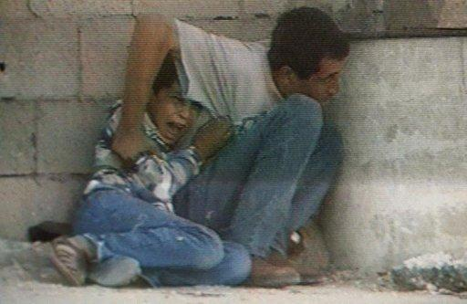 TV grab from France 2 shows Jamal Al-Dura and his 12-year-old son trying to protect themselves in September 29, 2000