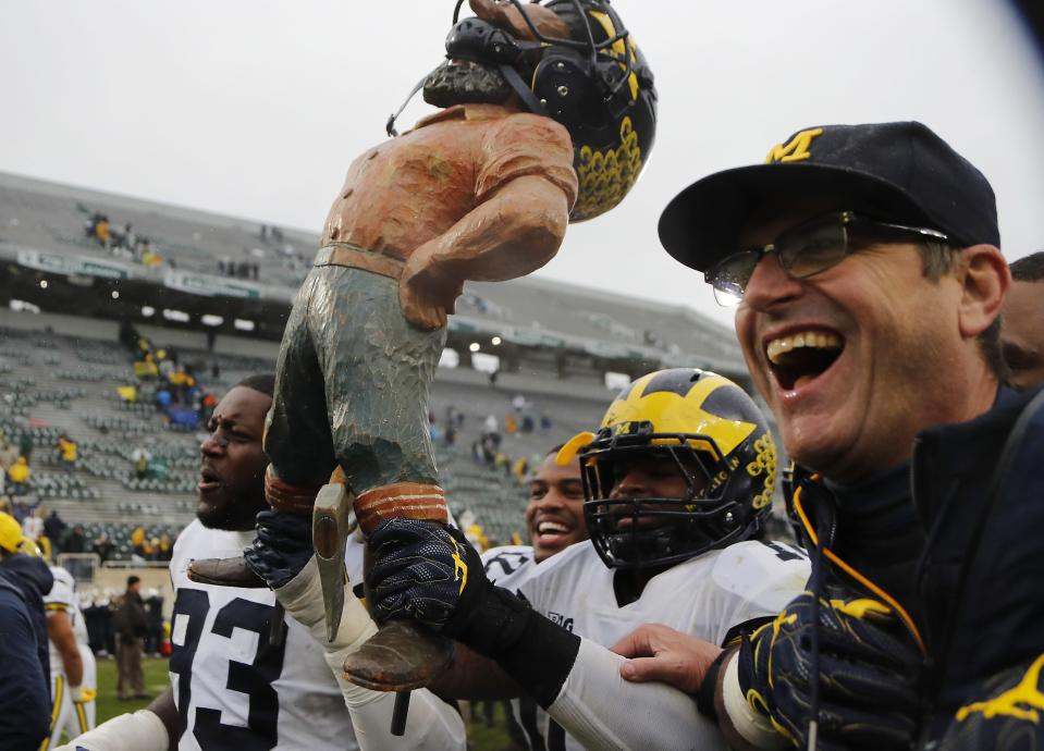 Michigan defensive lineman Lawrence Marshall (93), linebacker Devin Bush and head coach Jim Harbaugh walk off the field with the Paul Bunyan trophy after Michigan won 21-7. (AP)