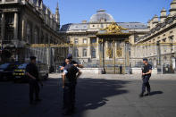 Police officers guard the Palace of Justice Wednesday, Sept. 8, 2021 in Paris. France on Wednesday will begin the trial of 20 men accused in the Islamic State group's 2015 attacks on Paris that left 130 people dead and hundreds injured. Among the plantiffs are nearly 1,800 victims, including survivors who suffered physical or psychological harm and families whose loved ones died that night. A total of 330 lawyers are representing them and the defendants. (AP Photo/Michel Euler)