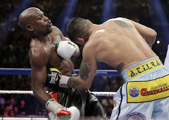 Marcos Maidana, right, from Argentina, connects with a left to the body of Floyd Mayweather Jr. in their WBC-WBA welterweight title boxing fight Saturday, May 3, 2014, in Las Vegas. (AP Photo/Isaac Brekken)