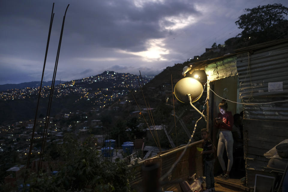 A woman looks at her smartphone outside of her home in the El Quilombo neighborhood of Caracas, Venezuela, Saturday, Feb. 13, 2021, amid the new coronavirus pandemic. (AP Photo/Matias Delacroix)