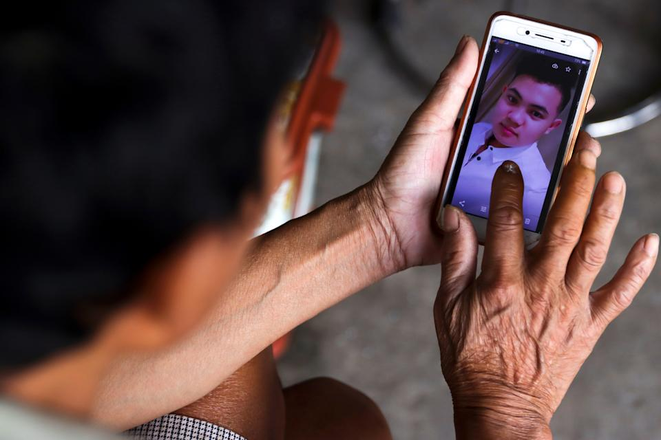 Hoang Van Lanh, father of Hoang Van Tiep, who is one of the suspected victims of the 39 people found dead in a refrigerated truck in Britain, shows his picture on a mobile phone at his house, in Dien Chau district, Nghe An province, Vietnam, October 28, 2019. REUTERS/Athit Perawongmetha