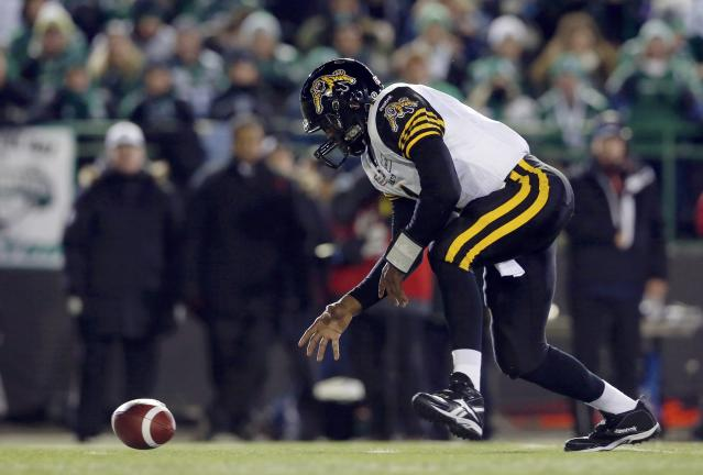 Hamilton Tiger-Cats quarterback Henry Burris reaches for the ball after missing a snap while playing against the Saskatchewan Roughriders during the first half of the CFL's 101st Grey Cup championship football game in Regina, Saskatchewan November 24, 2013. REUTERS/Mark Blinch (CANADA - Tags: SPORT FOOTBALL)