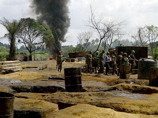 Members of the Joint Military Task Force search illegal oil refineries at Mbiama community in Nigeria's Bayelsa State on March 6, 2011
