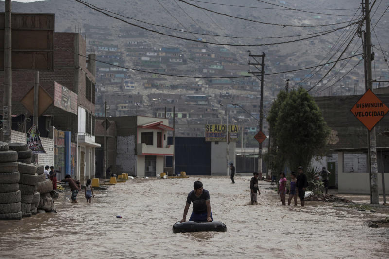 A man plays in a flooded street using an inner tube in Lima, Peru, Thursday, March 16, 2017. A new round of unusually heavy rains has killed at least a dozen people in Peru and now threatens flooding in the capital. Authorities said Thursday they expect the intense rains caused by the warming of surface waters in the eastern Pacific Ocean to continue another two weeks. (AP Photo/Rodrigo Abd)