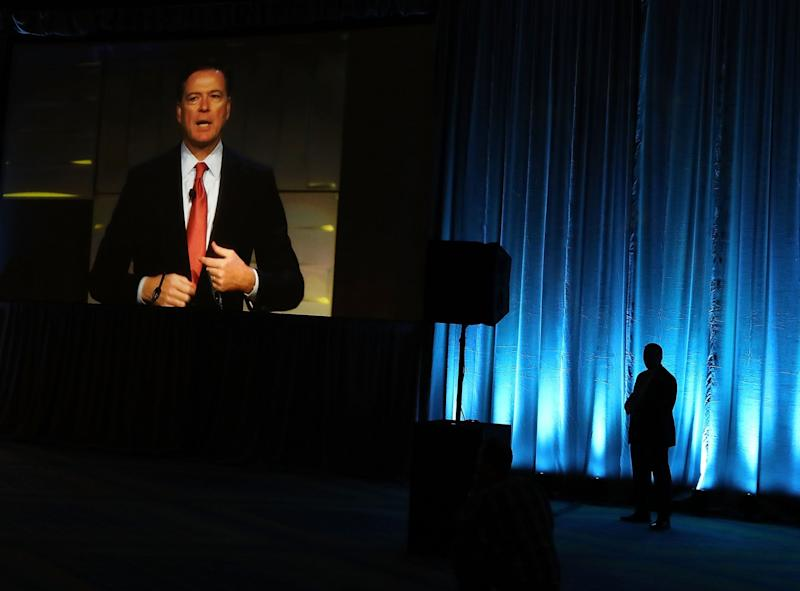 FBI Director James Comey is seen on a monitor speaking during a government symposium on cyber security, on August 30, 2016 in Washington, D.C. (Photo: Mark Wilson/Getty Images)