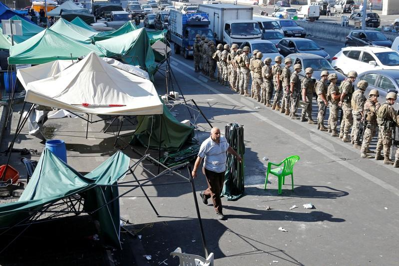 Man walks as Lebanese army soldiers stand guard in Beirut