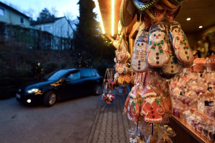 FILE PHOTO: A car drives past a booth with sweets at a drive-in Christmas market under a large marquee, amid the spread of the coronavirus disease
