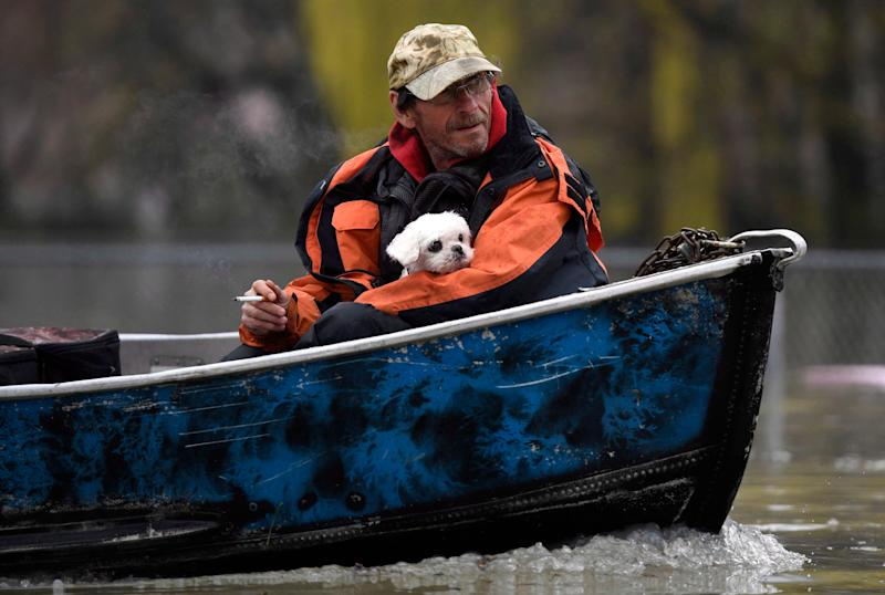 A man holds a dog as they navigate floodwaters by boat on Rue Saint-Louis in Gatineau, Que. on May 6. (The Canadian Press)