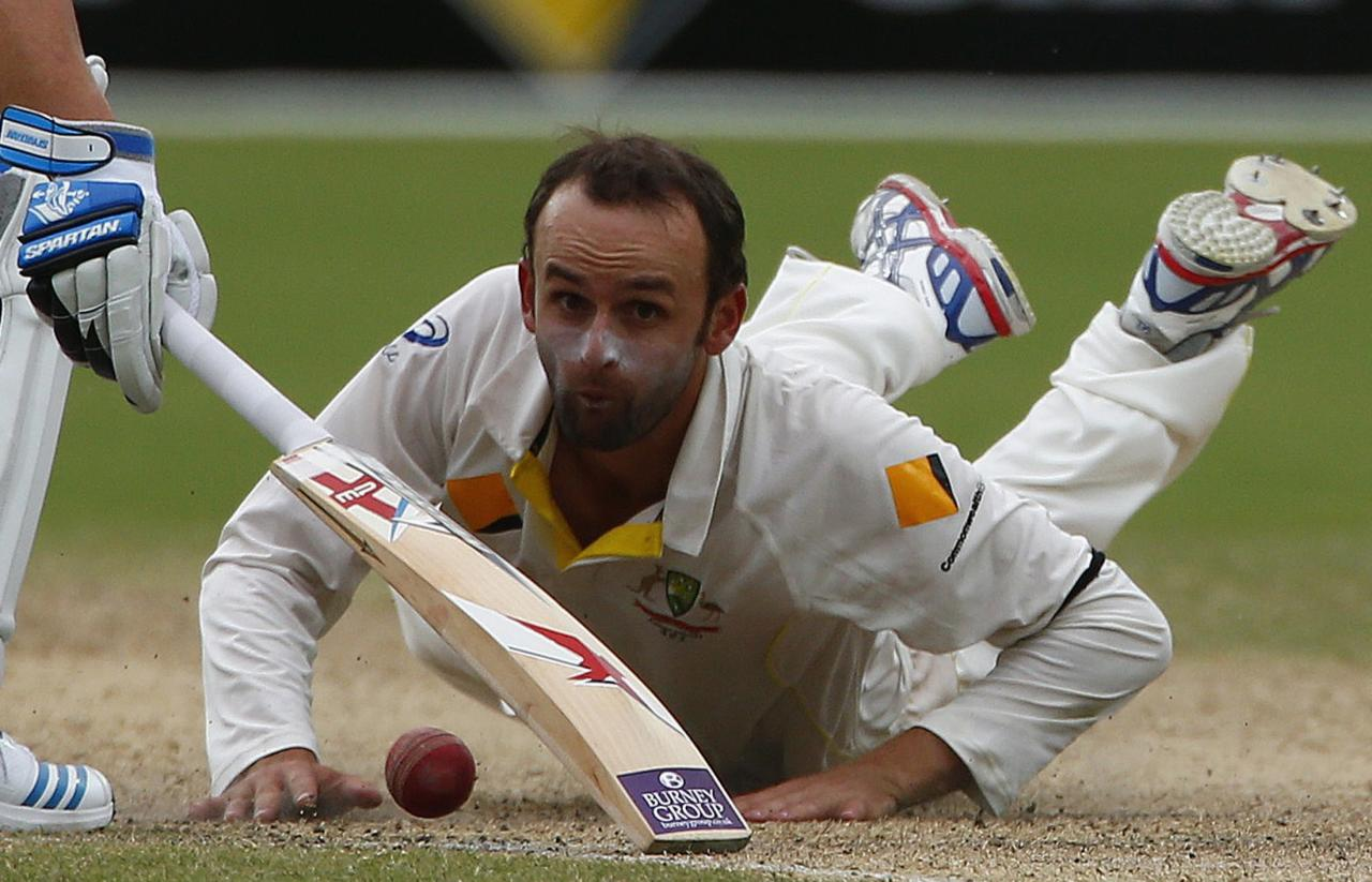 Australia's Nathan Lyon looks at the ball after a miss fielding hit by England's Ben Stokes during the fourth day's play in the second Ashes cricket test at the Adelaide Oval December 8, 2013.REUTERS/David Gray (AUSTRALIA - Tags: SPORT CRICKET)