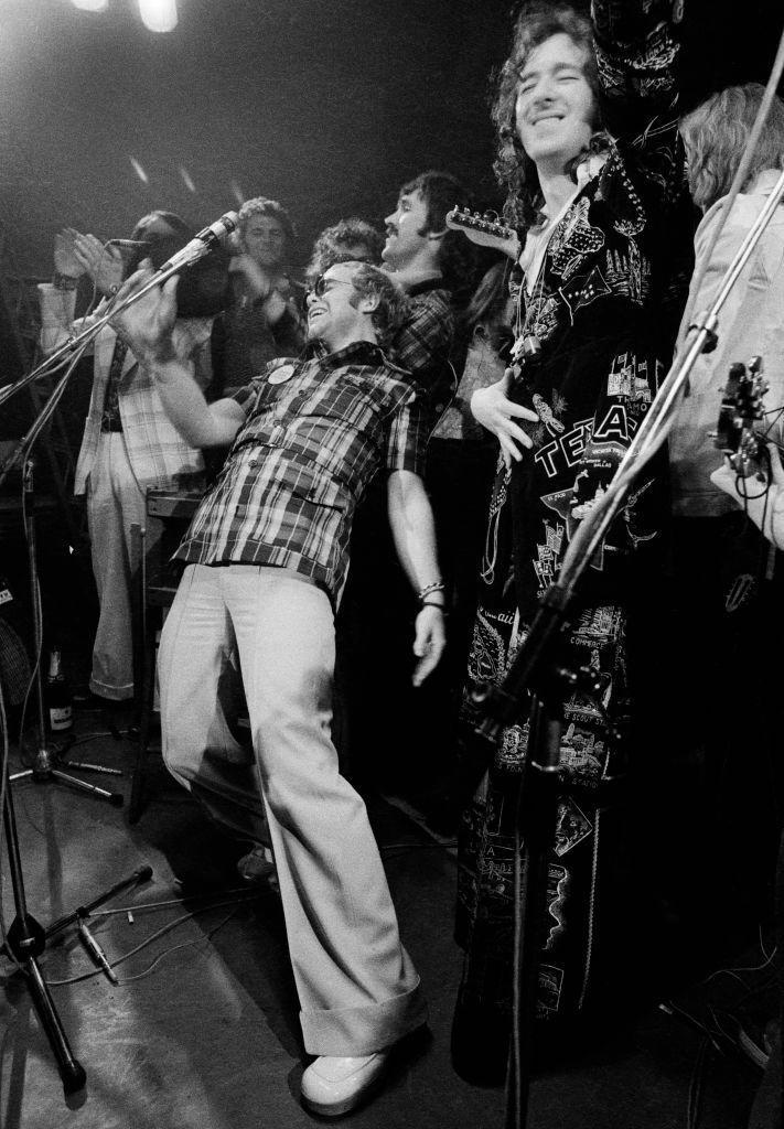 <p>Elton John takes center stage in a mosh pit as he performs at the Rocket Records launch party at the Moreton-in-Marsh village hall in Gloucestershire, England in 1973. </p>
