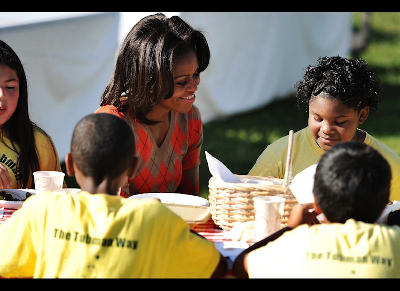 WASHINGTON, DC - OCTOBER 5: U.S. first lady Michelle Obama eats vegetable pizza after harvesting vegetables with local children from Bancroft and Tubman Elementary schools as they participate in the White House Kitchen Garden Fall Harvest, October 5, 2011 at the White House in Washington, DC. Michelle Obama planted the White House kitchen garden to help connect kids with the food they eat as part of her Let's Move! initiative. (Photo by Patrick Smith/Getty Images)