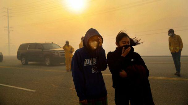 PHOTO: People cover their faces from the smoke created by the Easy Fire, Oct. 30, 2019, in Simi Valley, Calif. (Marcio Jose Sanchez/AP, FILE)