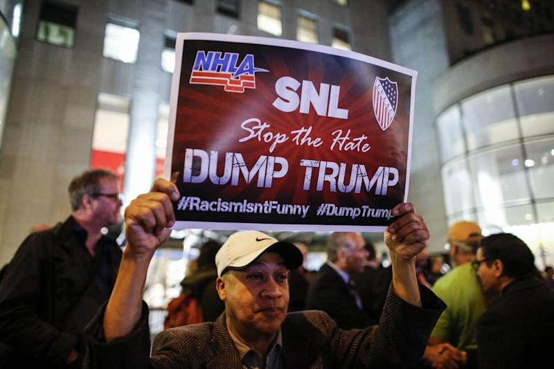 A man protests in front of NBC studios while other call calling for the network to rescind the invitation to Donald Trump to host Saturday Night Live show on November 4, 2015 in New York.