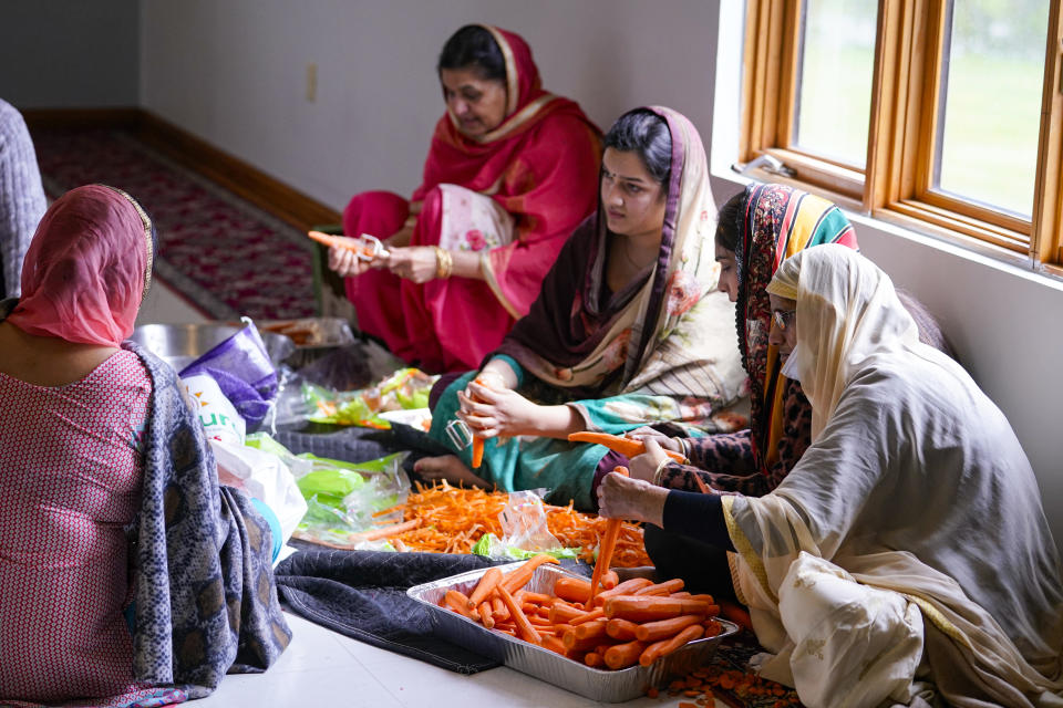 Members of the Sikh Satsang of Indianapolis prepare a communal meal in their Gurdwara building in Indianapolis, Saturday, April 17, 2021 where the Sikh Coalition held a meeting to formulate the groups response to the shooting at a FedEx facility in Indianapolis that claimed the lives of four members of the Sikh community. A gunman killed eight people and wounded several others before taking his own life in a late-night attack at a FedEx facility near the Indianapolis airport. (AP Photo/Michael Conroy)
