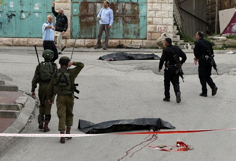 Israeli soldiers and police surround the bodies of two Palestinians who were killed in the West Bank town of Hebron, on March 24, 2016 (AFP Photo/Hazem Bader)