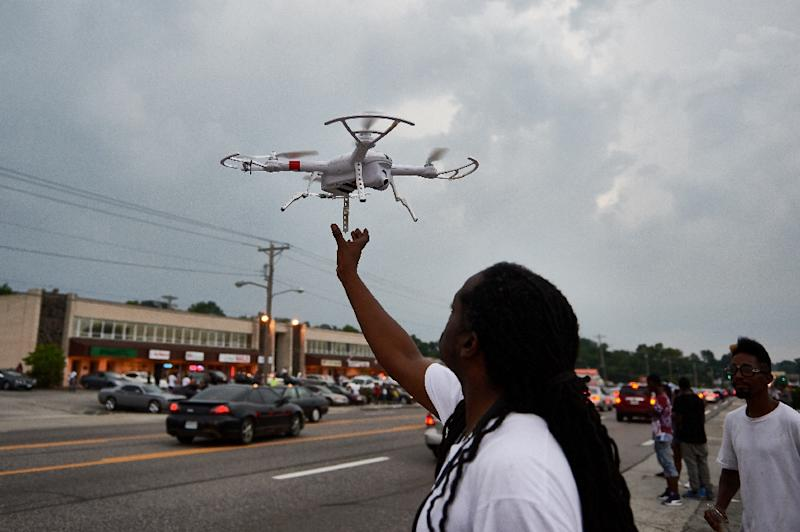 A man operates a remote control drone camera device prior to a protest march in Ferguson, Missouri on August 9, 2015 (AFP Photo/Michael B. Thomas)