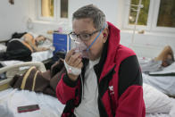 Florin Sandu, 72 years-old, holds an oxygen mask on his face at the COVID-19 unit of the Marius Nasta National Pneumology Institute in Bucharest, Romania, Thursday, Sept. 23, 2021. Daily new coronavirus infections in Romania, a country of 19 million, have grown exponentially over the last month, while vaccine uptake has declined to worrying lows. Government data shows that 91.5% of COVID-19 deaths in Romania between Sept. 18-23 were people who had not been vaccinated. (AP Photo/Vadim Ghirda)