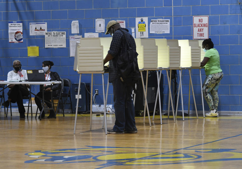 Troy Desole, 47, front, of Detroit, votes at Carstens Elementary Middle School at Remus Robinson in the state's primary election, Tuesday, Aug. 3, 2021, in Detroit. (Clarence Tabb Jr./Detroit News via AP)