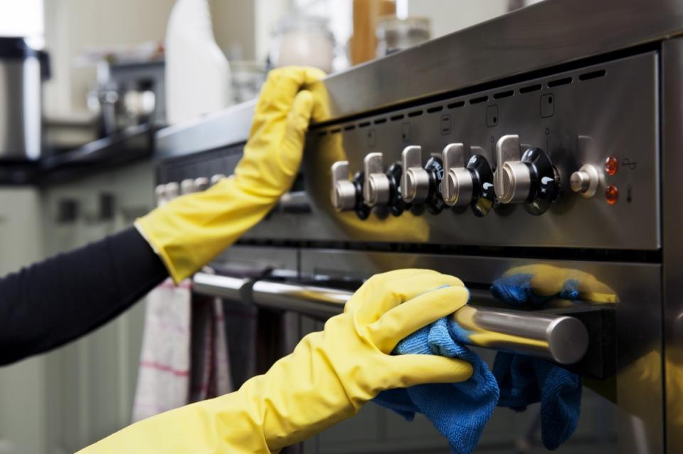 Closeup photograph of two hands cleaning the oven in a domestic kitchen.