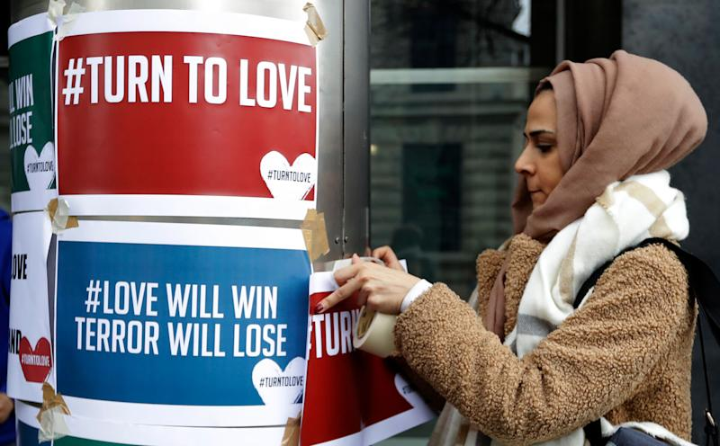 A demonstrator hangs banners from multi-faith group Turn to Love during a vigil at New Zealand House in London.