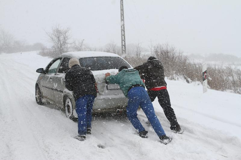 Image result for people pushing car in snowstorm