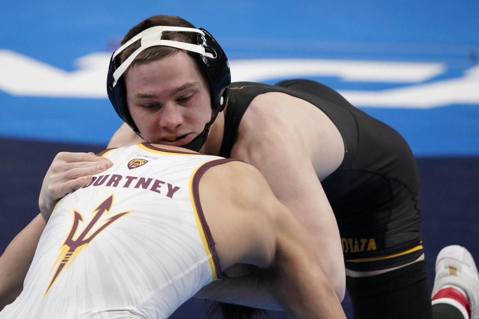 Iowa's Spencer Lee, top, takes on Arizona State's Brandon Courtney during their 125-pound match in the finals of the NCAA wrestling championships Saturday, March 20, 2021, in St. Louis. (AP Photo/Jeff Roberson)
