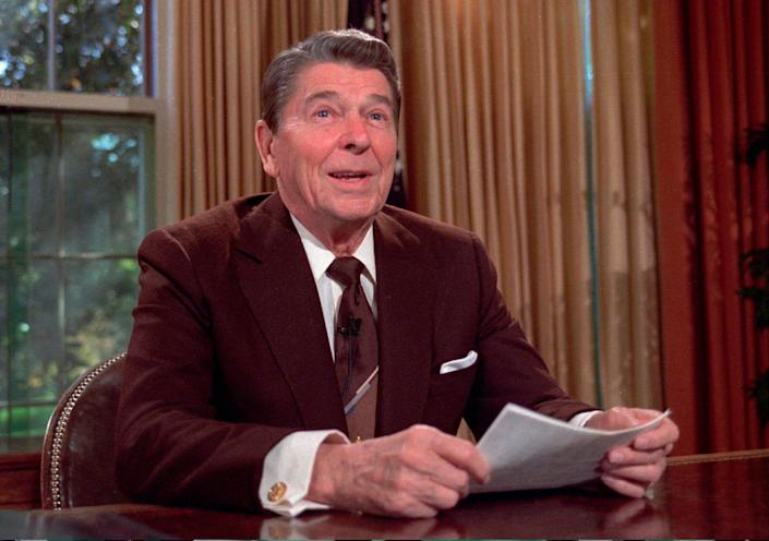 President Ronald Reagan works at his desk in the Oval Office of the White House as he prepares a speech on tax revision in Washington on May 24, 1985.