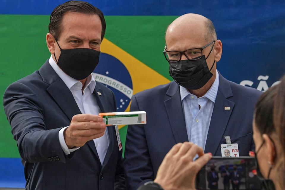Sao Paulo Governor Joao Doria (L) poses for a photo while holding a dose of the Coronavac vaccine as he stands next to the Butantan Institute director Dimas Covas, at the Guarulhos International Airport, in Sao Paulo, Brazil, on February 10, 2021. - Brazil received on February 10, 2021, a lot with 5,600 liters of the Coronavac vaccine, developed by the Chinese laboratory Sinovac Biotech. (Photo by NELSON ALMEIDA / AFP) (Photo by NELSON ALMEIDA/AFP via Getty Images)