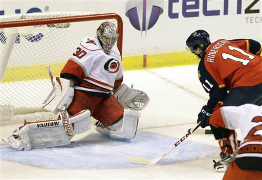 Florida Panthers center Jonathan Huberdeau (11), of Canada, scores his first goal as a Panther against Carolina Hurricanes goalie Cam Ward (30), also of Canada, during the first period of an NHL hockey game on Saturday, Jan. 19, 2013, in Sunrise, Fla. (AP Photo/Wilfredo Lee)