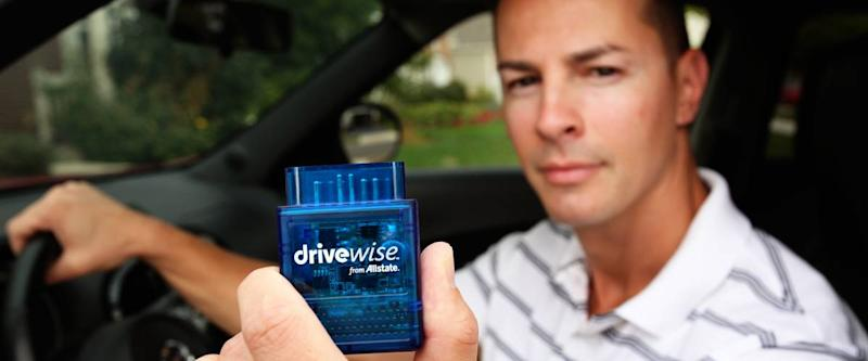 Young man holding the Allstate Drivewise dongle