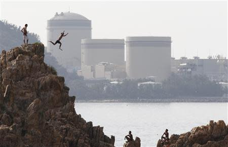 A man on vacation dives into the sea as Kansai Electric Power Co.'s Mihama nuclear power plant is seen in the background in Mihama town, Fukui prefecture, in this file picture taken July 2, 2011. REUTERS/Issei Kato
