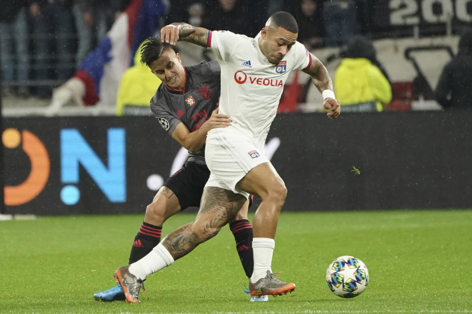 Lyon's Memphis Depay, right, vies for the ball with Benfica's Franco Cervi during the group G Champions League soccer match between Lyon and Benfica at the Lyon Olympic Stadium in Decines, outside Lyon, France, Tuesday, Nov. 5, 2019. (AP Photo/Laurent Cipriani)