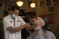 FILE - In this Feb. 23, 2021, file photo, a customer at Nashville Barber Shop gets a shave after coronavirus restrictions were eased in Jerusalem. While Israel provides a glimpse of what may be possible with high immunization rates, it also offers insight into the problems that lie ahead: Workplaces and schools are now grappling with what to do with those who refuse to get vaccinated. (AP Photo/Maya Alleruzzo, File)