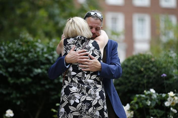 A man and woman embrace at a garden