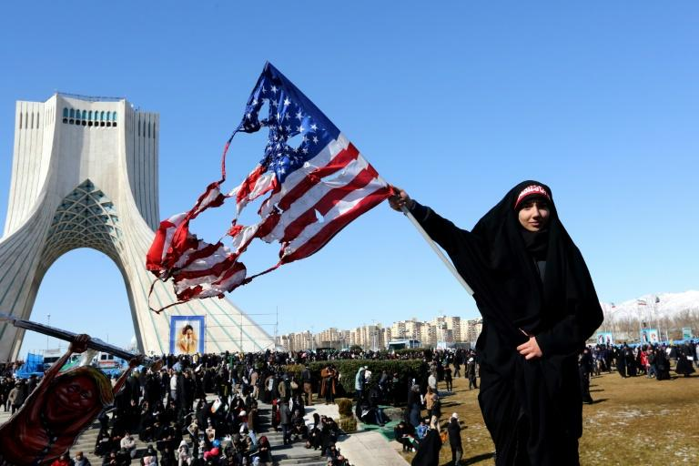 An Iranian woman marks the 41st anniversary of the Islamic republic by burning the US flag in Tehran's Azadi Square