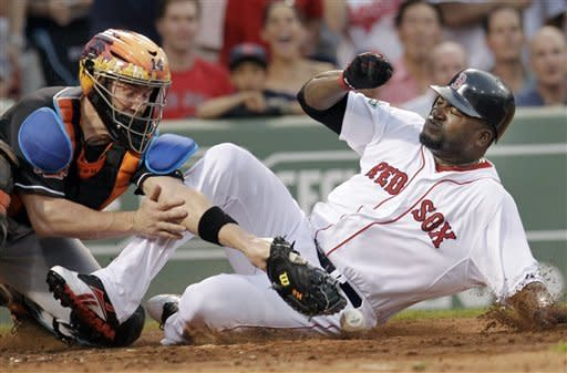 Miami Marlins catcher John Buck reaches for the ball as Boston Red Sox designated hitter David Ortiz slides safely into home on a hit by Cody Ross during the third inning of an interleague baseball game at Fenway Park in Boston on Wednesday, June 20, 2012. (AP Photo/Elise Amendola)