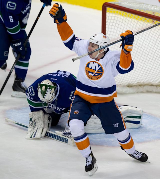 New York Islanders' Casey Cizikas, right, celebrates after Matt Martin scored the team's fifth goal as Vancouver Canucks' goalie Eddie Lack, of Sweden, kneels on the ice during third period NHL hockey action in Vancouver, British Columbia, on Monday March 10, 2014. (AP Photo/The Canadian Press, Darryl Dyck)