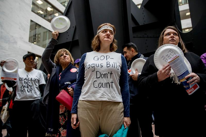 "A furloughed government worker wears a shirt that reads ""GOP Bogus Bills Don't Count"" during a silent protest against the ongoing partial government shutdown on Capitol Hill in Washington, Wednesday, Jan. 23, 2019. Protesters held up disposable plates instead of posters to avoid being arrested. (AP Photo/Andrew Harnik)"