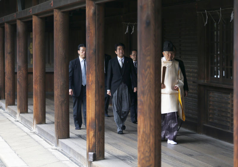 "Japanese Prime Minister Shinzo Abe, second from left, is led by a Shinto priest, right, after paying respect for the war dead at Yasukuni Shrine in Tokyo Thursday, Dec. 26, 2013. Abe visited Yasukuni war shrine in a move sure to infuriate China and South Korea. The visit to the shrine, which honors 2.5 million war dead including convicted class A war criminals, appears to be a departure from Abe's ""pragmatic"" approach to foreign policy, in which he tried to avoid alienating neighboring countries. It was the first visit by a sitting prime minister since Junichiro Koizumi went to mark the end of World War II in 2006. (AP Photo/Shizuo Kambayashi)"