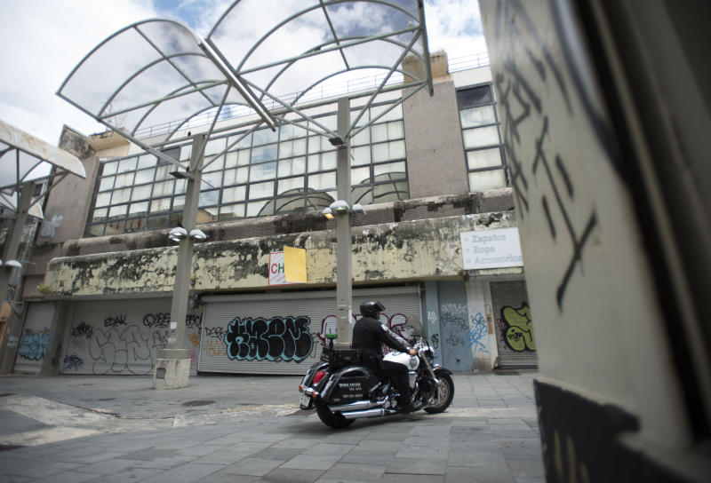A municipal police officer drives past shuttered shops in the Paseo de Diego of San Juan, Puerto Rico, Wednesday, April 17, 2019. Many Puerto Ricans have left for Florida and New York. (AP Photo/Carlos Giusti)