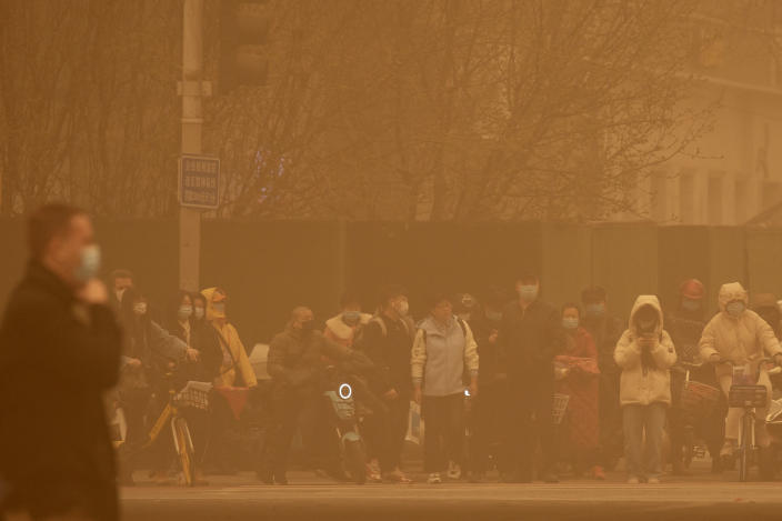People wait to cross an intersection amid a sandstorm during the morning rush hour in Beijing, Monday, March 15, 2021. The sandstorm brought a tinted haze to Beijing's skies and sent air quality indices soaring on Monday. (AP Photo/Mark Schiefelbein)
