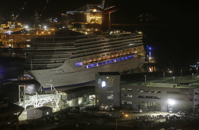 The cruise ship Carnival Triumph is pushed towards the cruise terminal along the Mobile River in Mobile, Ala., Thursday, Feb. 14, 2013. The ship with more than 4,200 passengers and crew members was idled for nearly a week in the Gulf of Mexico following an engine room fire. (AP Photo/Dave Martin)
