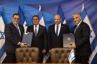 Israeli Prime Minister Naftali Bennett, second right, and Honduran President Juan Orlando Hernandez, second left, look on as Israeli Foreign Minister Yair Lapid, right, and Honduran Foreign Minister Lisandro Rosales hold signed agreements between their two countries at the prime minister's office, in Jerusalem, Thursday, June 24, 2021. (Heidi Levine/Pool via AP).