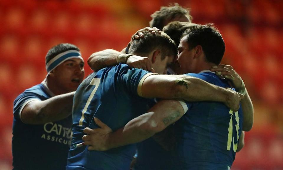 Italy's Johan Meyer (centre) celebrates scoring a try against Wales.