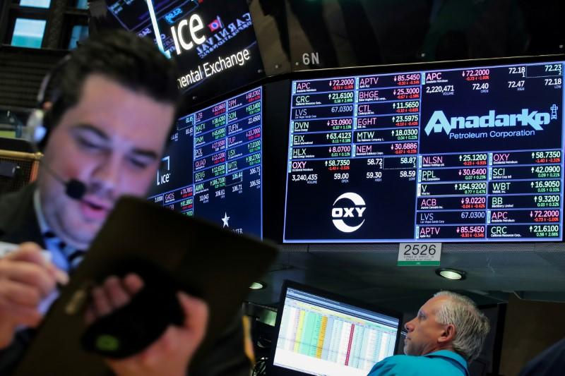 FILE PHOTO: Traders work on the floor by the post that trades Anadarko Petroleum and Occidental Petroleum at the NYSE in New York