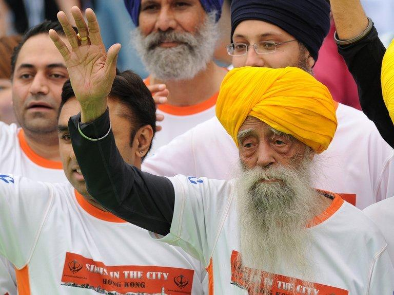 Fauja Singh waves after crossing the finish line in the 10km event as part of the Hong Kong Marathon on February 24, 2013. The 101-year-old Sikh is believed to be the world's oldest distance runner